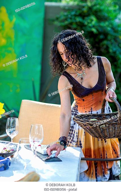 Mature woman preparing garden table for party
