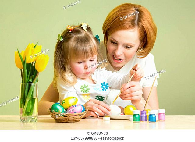 happy mother teaches child daughter to paint easter eggs