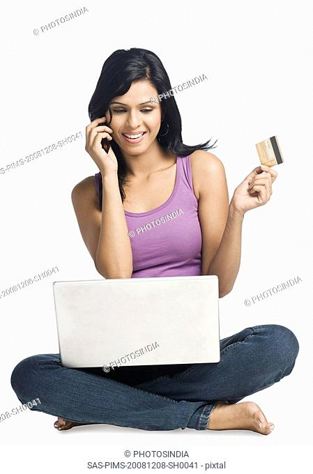 Woman shopping online and talking on a mobile phone