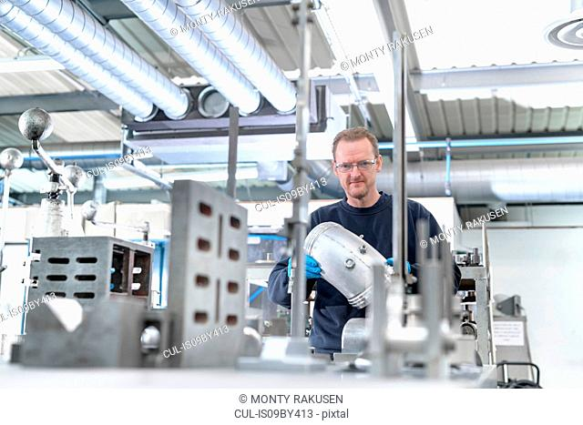Portrait of engineer inspecting parts in engineering factory