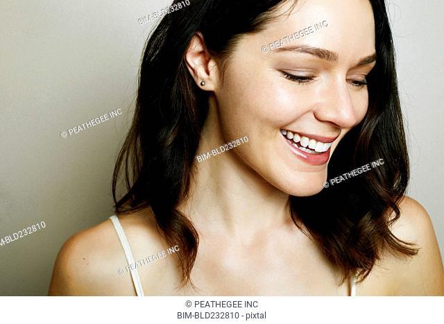 Caucasian woman laughing near wall
