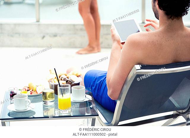 Man relaxing by pool using digital tablet