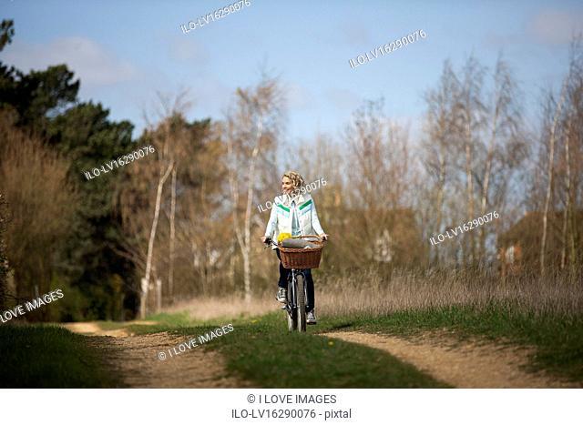 A mature woman cycling along a country path