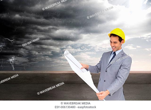 Composite image of smiling architect with hard hat looking at plans