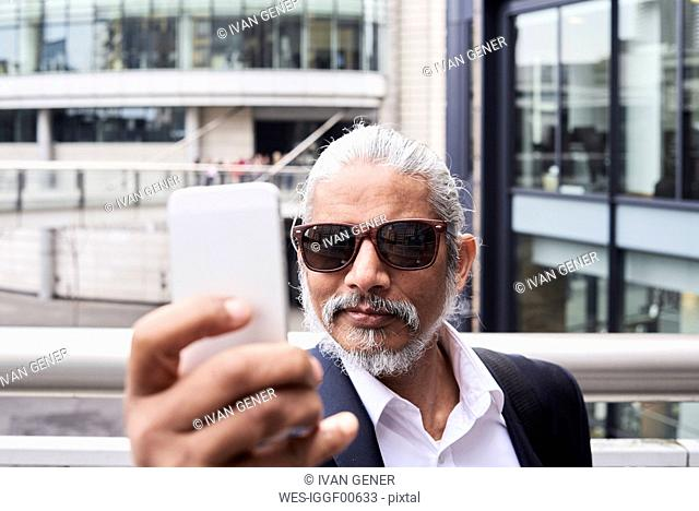 Portrait of grey-haired senior businessman taking selfie with smartphone