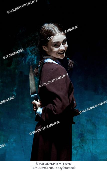 Portrait of a young girl with knife in school uniform as killer woman against school board . The image in the style of Halloween and Addams family