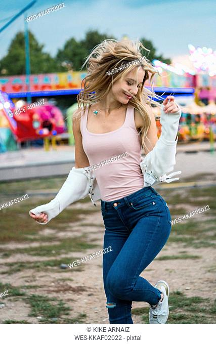 Happy young woman moving on a funfair