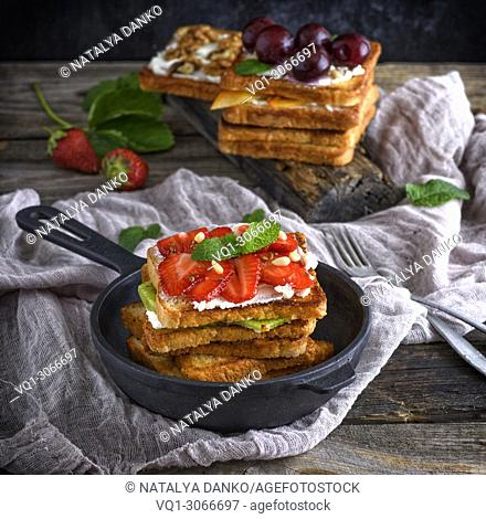 Pile of French toast from white bread with cottage cheese, strawberries, kiwi in a black cast-iron round frying pan with a handle on a gray wooden table