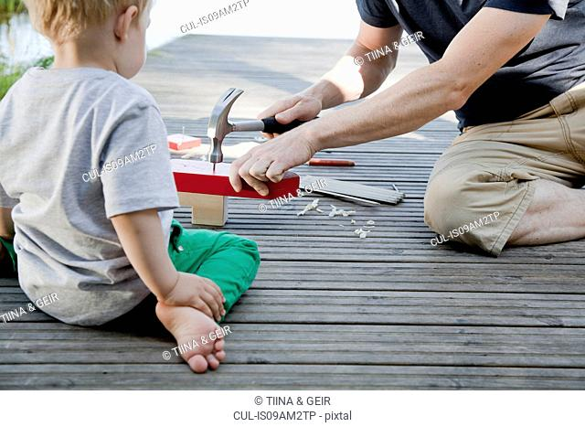 Male toddler watching father make toy boat on pier