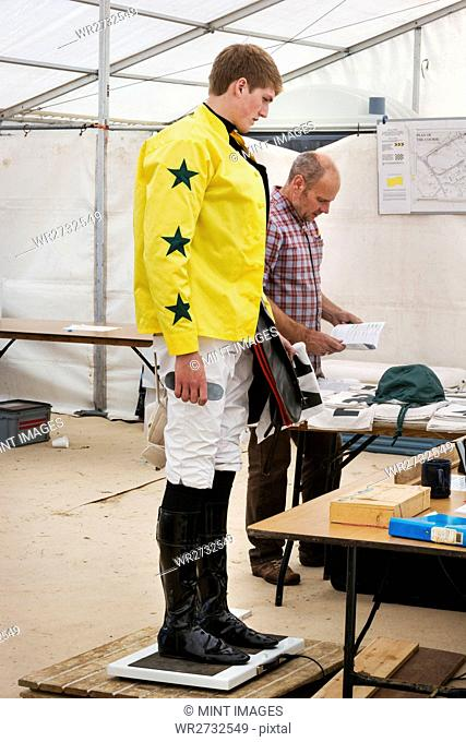 Jockey in a yellow shirt standing on weighing scale, being weighed before a horse race
