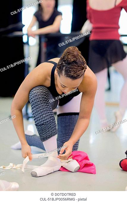 Ballet dancer tying on pointe shoes