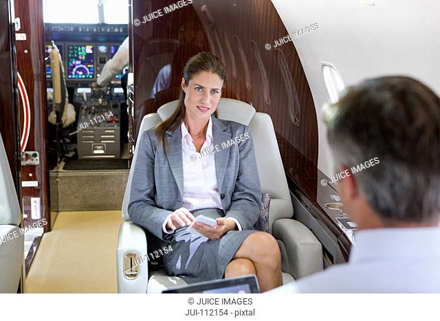 Businesswoman with phone and Businessman with digital tablet having meeting on private jet