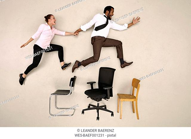 Businessman jumping with his female colleague over chairs