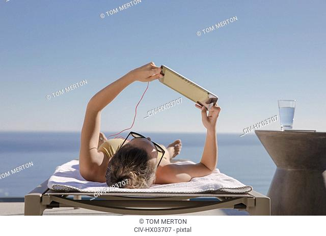 Woman sunbathing, using digital tablet on lounge chair on sunny patio with ocean view