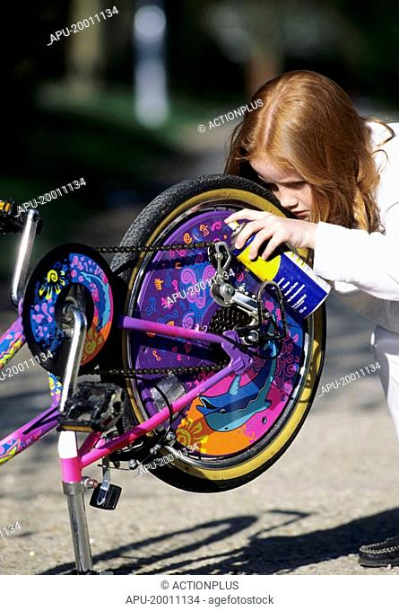Girl working on her bike chain with oil spray