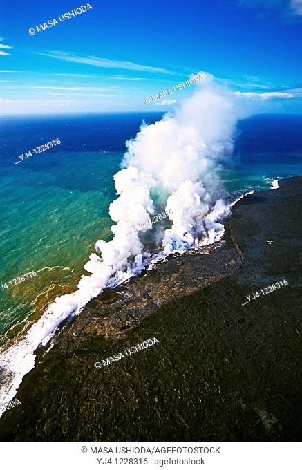 aerial view of lava ocean entry - hot molten lava fed from multiple underground lava tubes, creating massive steam clouds as it enters cold ocean
