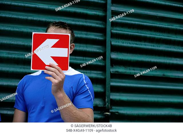 Man holding a arrow signboard in his hand