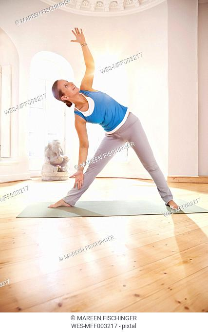 Woman in extended triangle pose in sunny yoga studio