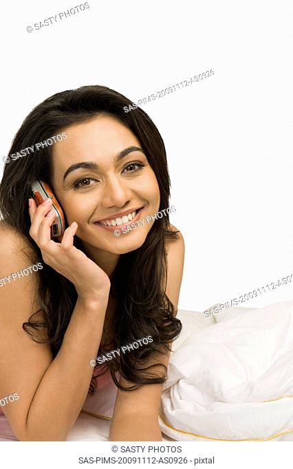 Portrait of a woman lying on the bed and talking on a mobile phone
