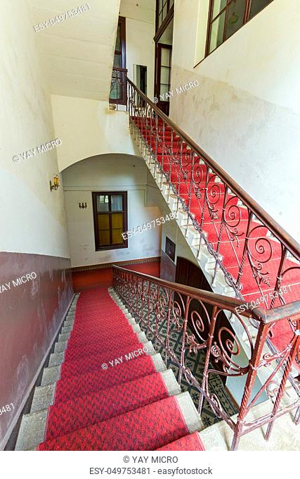 Stair flights in the building between the floors with red carpet. Painted walls and chandeliers in candlesticks on them