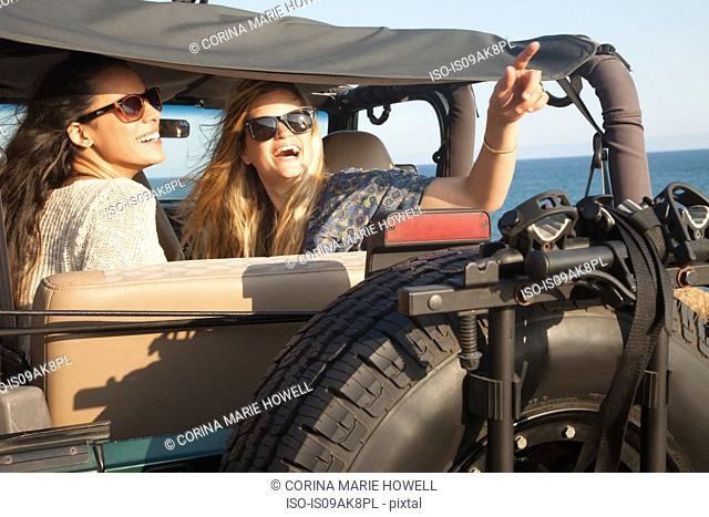 Two young women looking up from jeep at coast, Malibu, California, USA