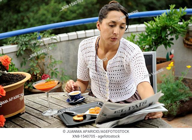 Young woman having breakfast on a terrace