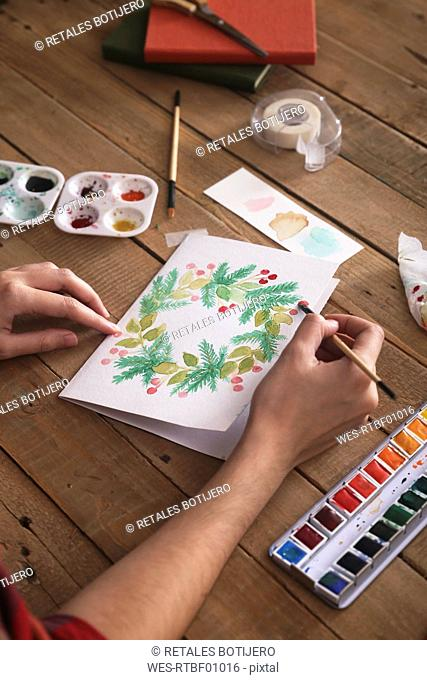 Young woman painting Christmas card with water colors, close-up