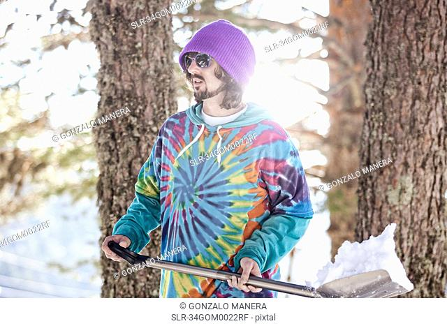 Man in hoody shoveling snow