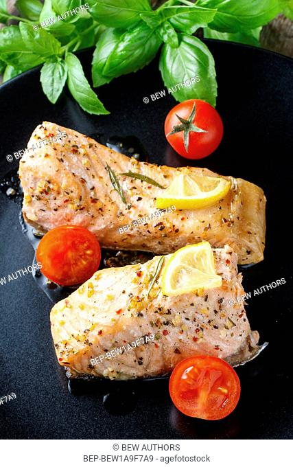 Baked salmon with herbs on the black plate. Healthy food