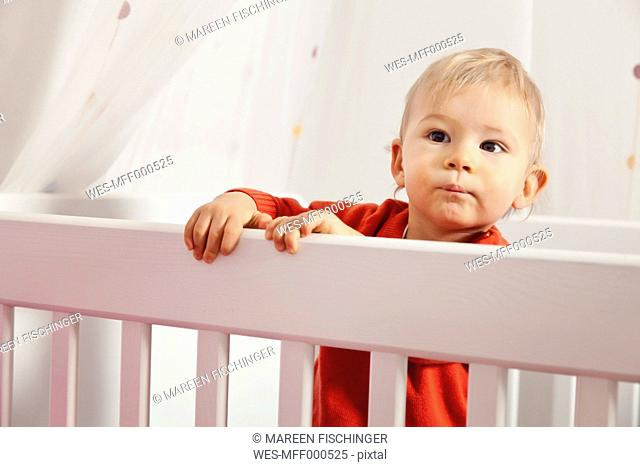 Germany, Bonn, Boy standing in his bed