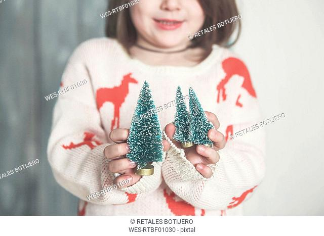 Little girl with miniature Christmas tree, close-up