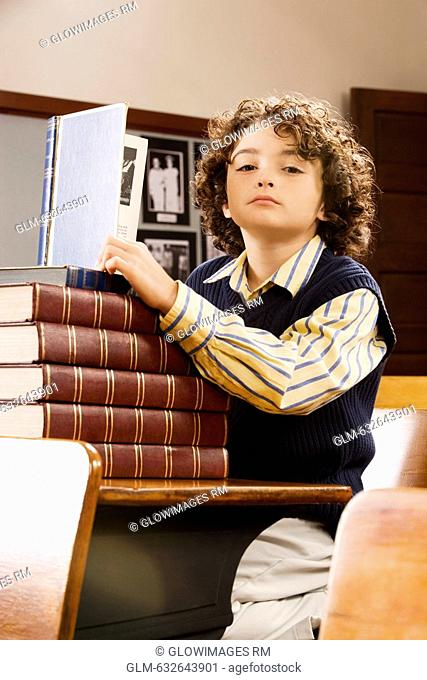 Schoolboy holding a book in a classroom