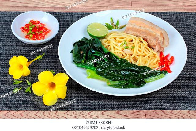 """Fried Japanese noodle as """"""""Ramen"""""""" topped Chinese kale and streamed streaky pork in soup with halve green lemon and sliced chili and minced chili in sour sauce..."""