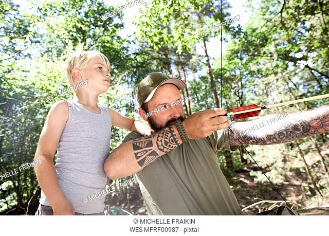 Son watching father shooting with bow and arrow in the forest