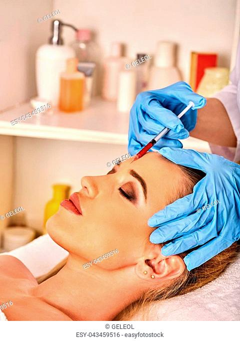 Filler injection for female forehead face. Plastic aesthetic facial surgery in beauty clinic. Doctor in medical gloves with red syringe injects cheeks drug