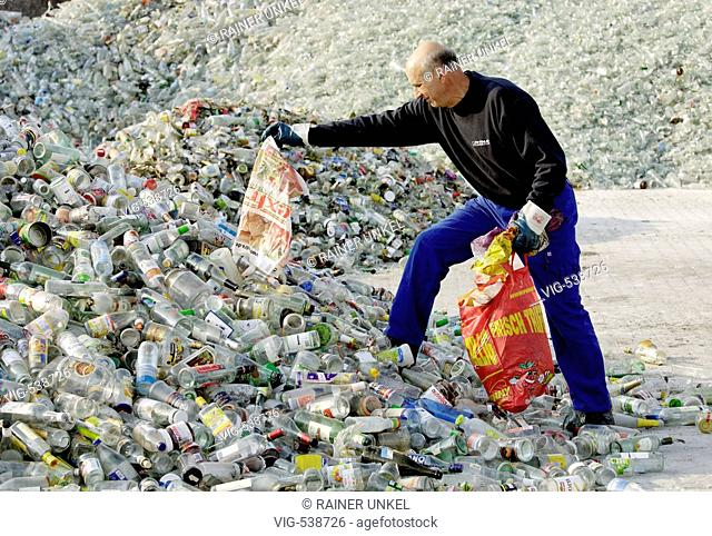 GERMANY, KOBLENZ, 16.10.2007, Glassrecycling at Rhenus company in Koblenz. worker picking plastic bags from a heep of bottles