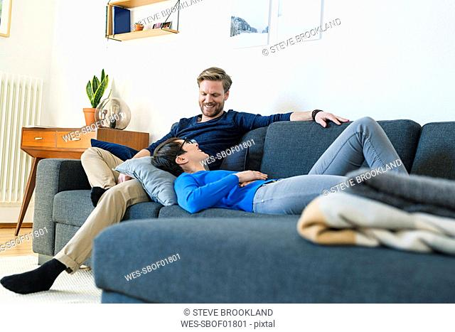 Happy casual couple relaxing on lounge couch in their modern living room