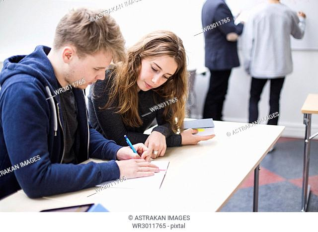 Two students leaning over desk