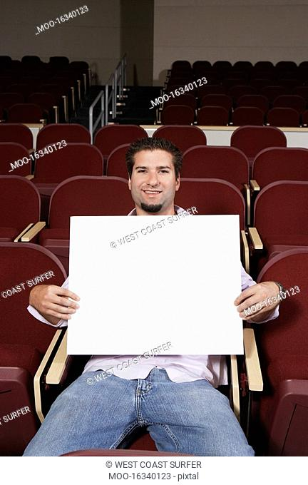 Male student holding blank board in lecture theatre portrait