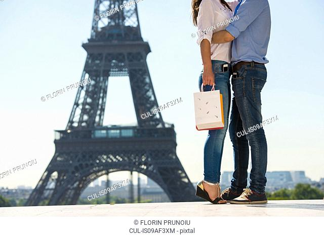 Young couple embracing in front of Eiffel Tower, Paris, France