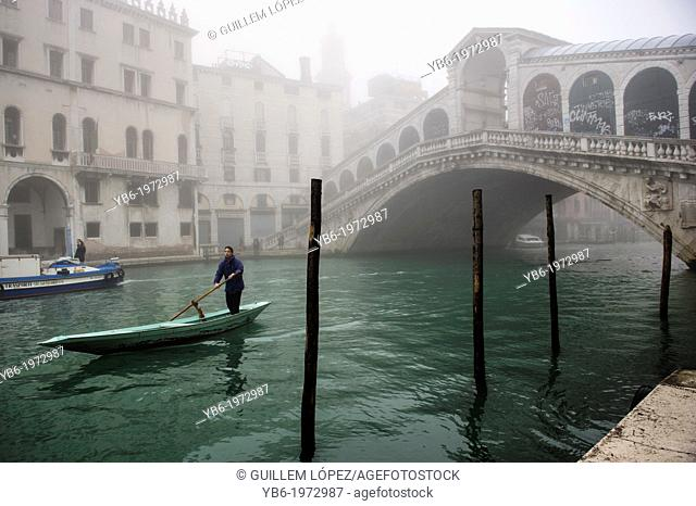 A man rowing along the Grand Canal and the Rialto Bridge in Venice Covered in thick fog, Italy
