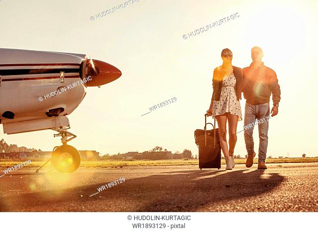 Young couple with luggage, propeller airplane in foreground