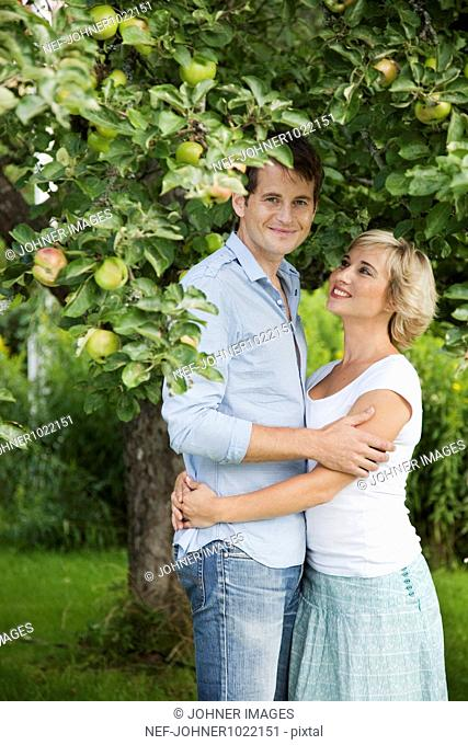Portrait of couple by apple tree