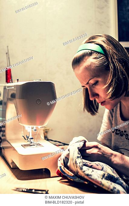 Caucasian woman using sewing machine
