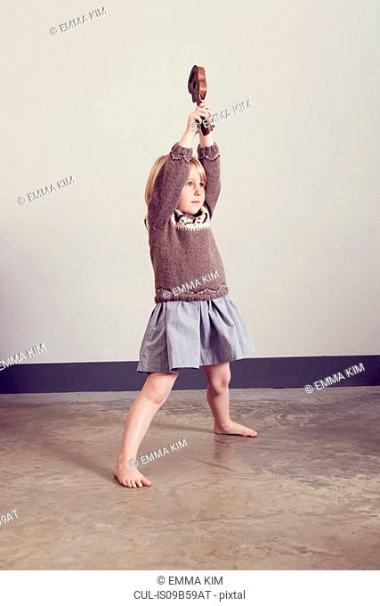 Girl playing holding up old wooden toy guitar