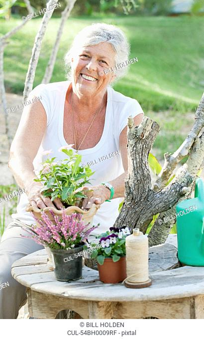 Older woman arranging flowers outdoors
