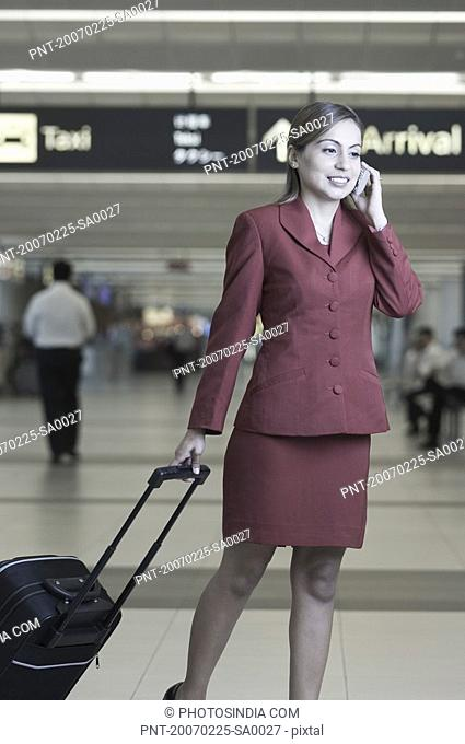 Businesswoman pulling her luggage while talking on a mobile phone