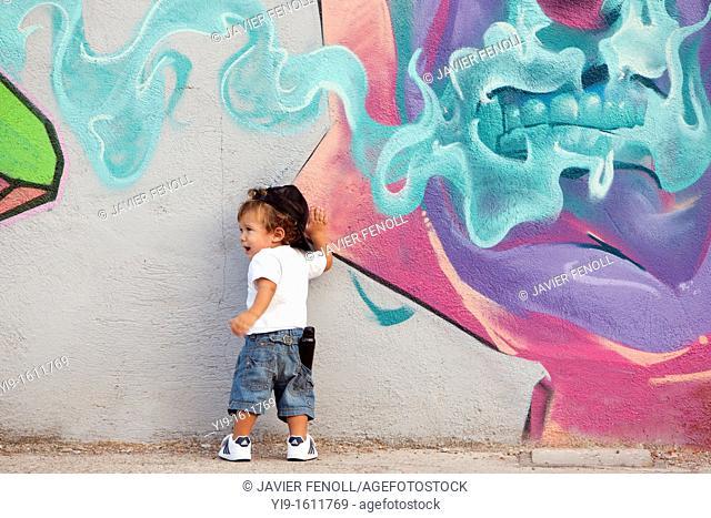 boy painting graffiti on the wall