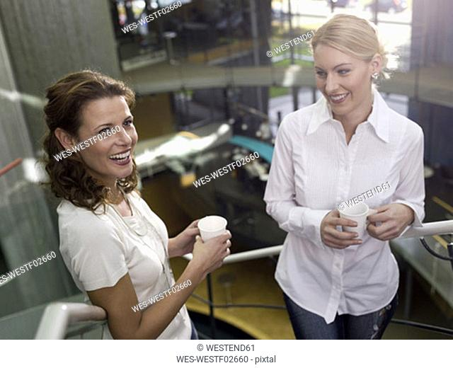Two woman on steps, holding paper cups