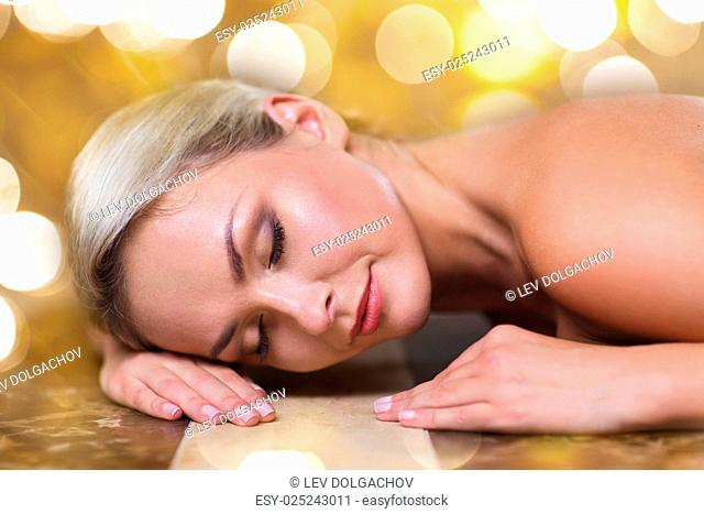 people, beauty, spa, healthy lifestyle and relaxation concept - beautiful young woman lying on hammam table in turkish bath over holidays lights background